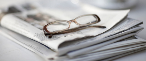 Newspaper folded with glasses on top