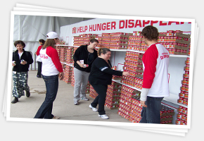 volunteers building the word hunger out of soup cans